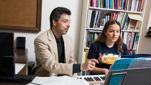 Music professor Justin Morrell teaches a keyboard lesson to a student