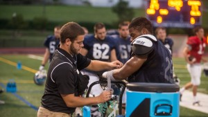 LVC athletic training student assists a football player on Arnold Field