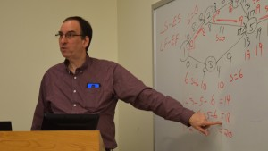 Lewis Chasalow, professor of Business and Economics, reviews a problem with his class