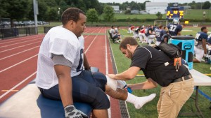 LVC football player gets his ankle taped by student athletic trainer