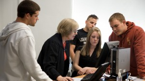 Sociology professor Marianne Goodfellow collaborates with a group of students on their project
