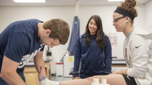 Student athletic trainer tapes a student's ankle as part of the athletic training program