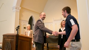 Professor of French, Rick Chamberlin congratulates a student on his departmental award