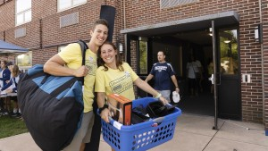 A student poses with items from move in day.