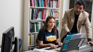 A professor assists an LVC music major with their composition on a keyboard