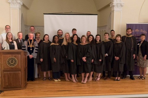 MBA graduates pose for a group photo during the Hooding Ceremony and Reception
