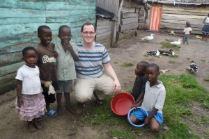 Patrick Maxwell poses with children in the Ugandan village of Sitabaale