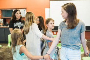 LVC alum Angie Magazino preforms an activity with young girls